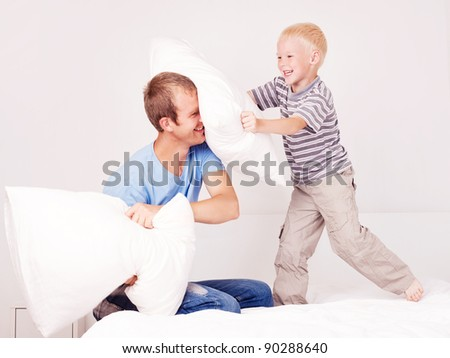 happy laughing father and  son having a pillow fight in bed at home (focus on the man) - stock photo