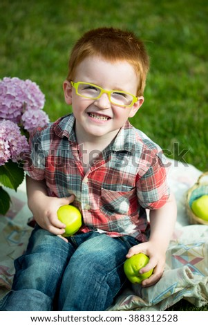 Happy laughing funny little red haired boy in stylish checkered shirt jeans and yellow glasses sitting outdoor on picnic with green apples near pink flowers on natural backdrop, vertical picture - stock photo