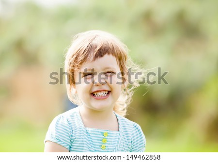 happy laughing girl against green grass meadow - stock photo