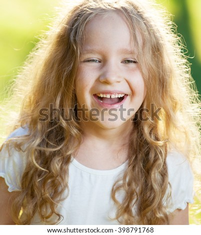 Happy laughing girl on grass. Smiling one child outdoors - stock photo