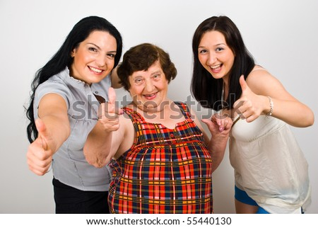 Happy laughing grandma with her granddaughter standing in a row and giving thumbs up - stock photo