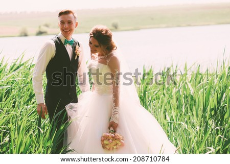 happy laughing groom and bride near pond - stock photo
