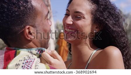 Happy laughing Hispanic woman embracing boyfriend at the pool - stock photo