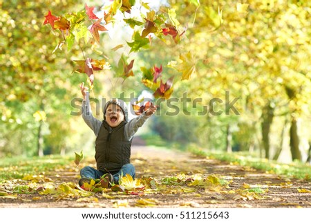 happy laughing kid throwing autumn fall leaves in an autumn alley