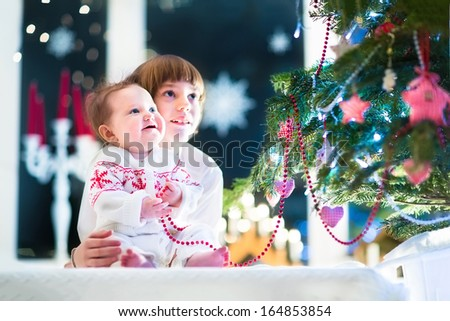 Happy laughing kids, a school age boy and his baby sister, playing under a beautiful Christmas tree in a dark living room - stock photo