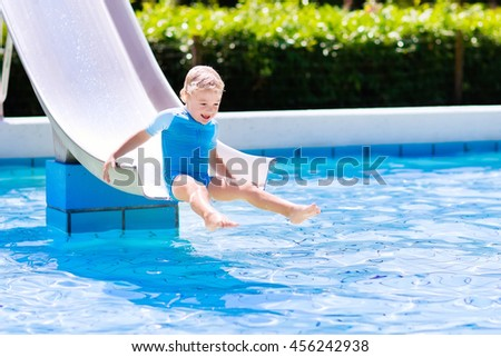 Happy laughing little boy playing on water slide in outdoor swimming pool on a hot summer day. Kids learn to swim. Child wearing sun protection rash guard sliding on aqua playground in tropical resort - stock photo
