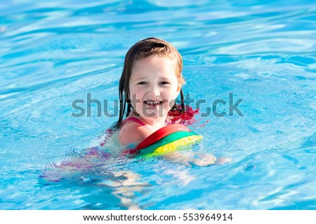 Happy laughing little girl playing in outdoor swimming pool on a hot summer day. Kids learn to swim with colorful floaties