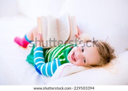 Happy laughing little girl reading a book relaxing on a white couch at home - stock photo