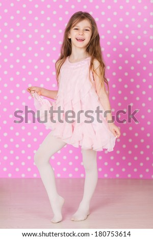 happy laughing little long hair girl dancing on pink background - stock photo