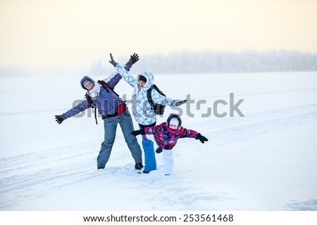 Happy laughing mature woman, young woman and girl posing on frozen winter lake - stock photo