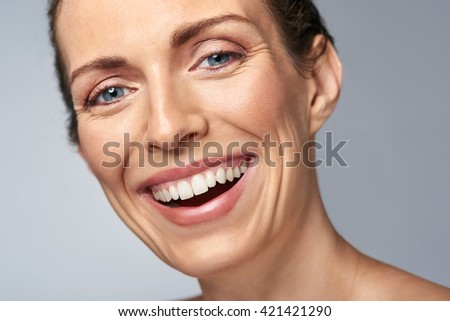 Happy laughing middle age woman in studio, isolated on grey - stock photo