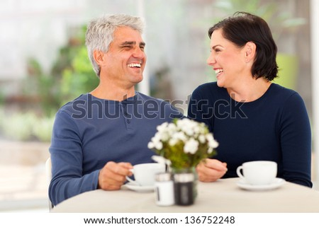 happy laughing middle aged couple enjoying tea at home - stock photo