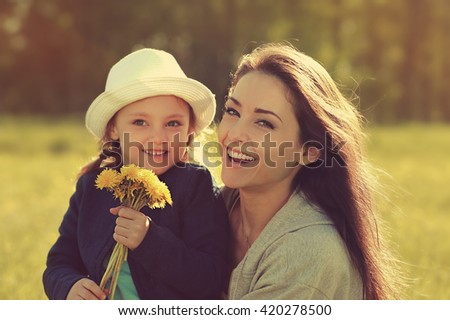 Happy laughing mother embracing her daughter with yellow bright flowers on summer background - stock photo