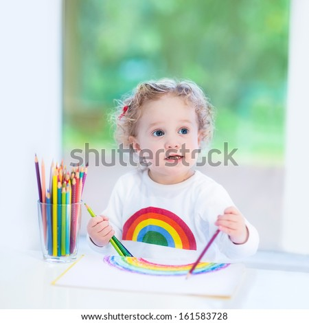 Happy laughing toddler girl drawing next to a window into the garden - stock photo