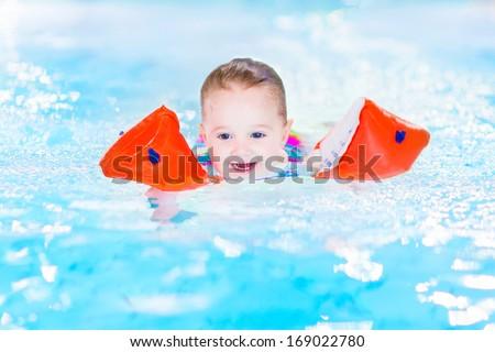 Happy laughing toddler girl having fun in a swimming pool - stock photo