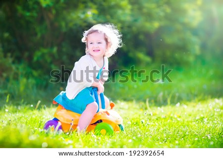 Happy laughing toddler girl in a blue dress having fun playing in the garden riding a yellow toy car enjoying sunny weather on a warm windy summer day - stock photo