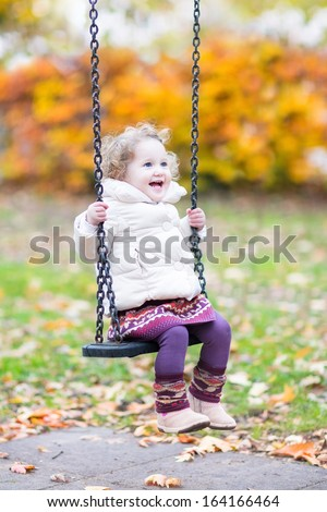 Happy laughing toddler girl playing on a swing with golden autumn trees in the background - stock photo