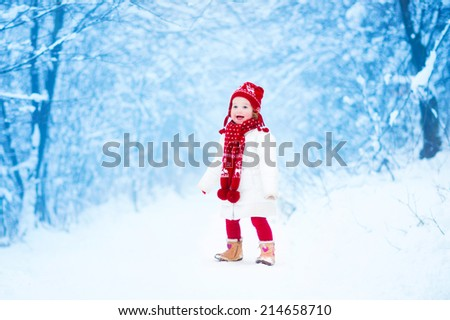 Happy laughing toddler girl wearing a white down jacket and red knitted hat and scarf playing and running in a beautiful snowy winter park on Christmas day - stock photo