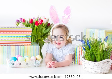 Happy laughing toddler girl with curly hair wearing a blue dress and bunny ears playing with Easter presents, eggs and colorful spring flowers, on white background - stock photo