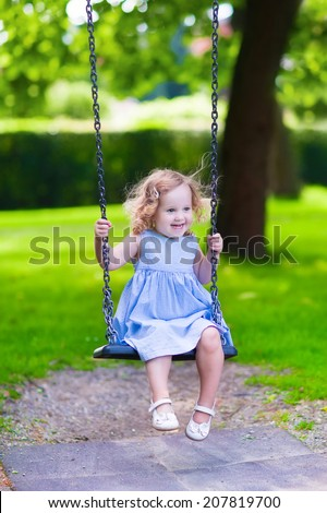 Happy laughing toddler girl with curly hair wearing a blue dress enjoying a swing ride on a sunny summer playground in a park  - stock photo