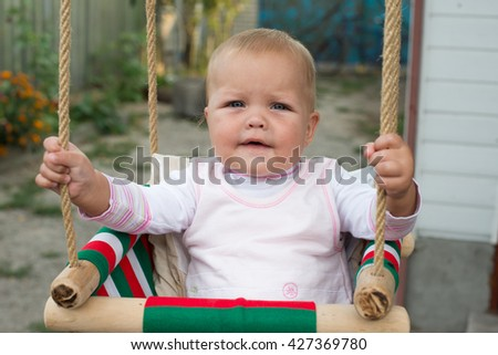 Happy laughing toddler girl with curly hair wearing a blue dress enjoying a swing ride on a sunny summer playground in a park
