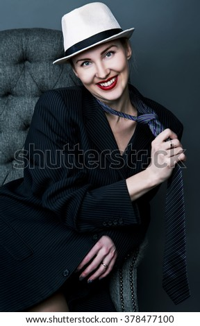happy laughing woman wearing a suit and a hat, against red studio background