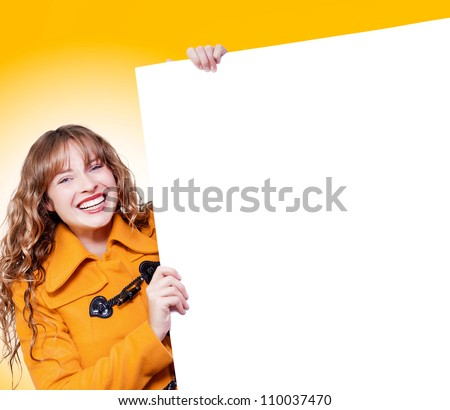Happy laughing young blonde woman in a warm bright orange winter coat holding up a blank white board from the side for your text or advertisement - stock photo