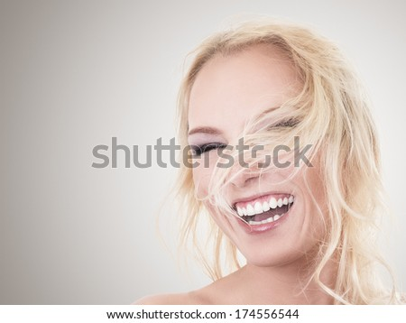 Happy laughing young blonde woman studio portrait - stock photo