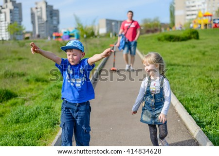 Happy laughing young boy and girl running outdoors along a path through an urban park in spring sunshine followed by their father in the background - stock photo