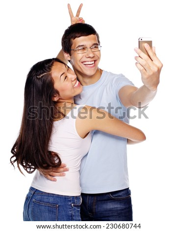 Happy laughing young couple joking and taking photo of themselves with smartphone on isolated white background - stock photo