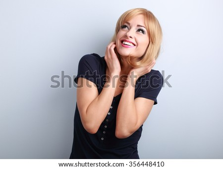 Happy laughing young woman with blond hair style looking up on blue background - stock photo