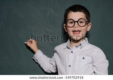 Happy learner. Cheerful little schoolboy in glasses standing near the blackboard and smiling - stock photo