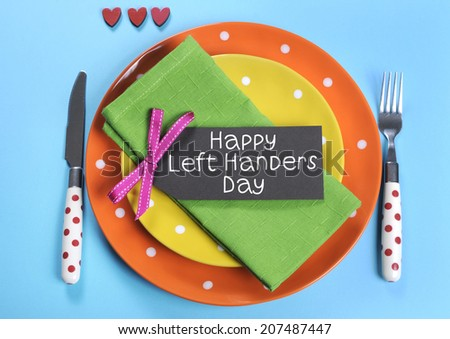 Happy Lefthanders Day, for August 13, International Left-handers Day, with colorful table setting showing reverse cutlery placing, in orange, yellow, pale blue and green polka dot colors.