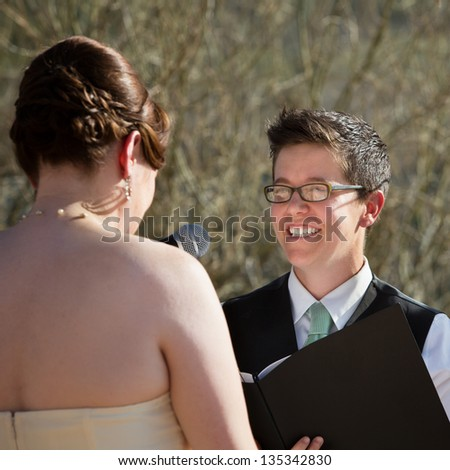 Happy lesbian lady reading vows to bride - stock photo