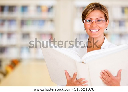 Happy librarian holding a book and smiling at the library - stock photo