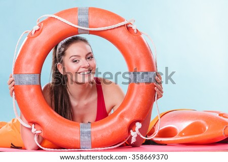 Happy lifeguard with ring buoy lifebuoy. Woman girl supervising swimming pool water. Accident prevention. - stock photo