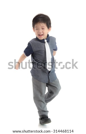 Happy little asian boy in school uniform on white background isolated