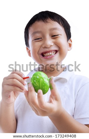 Happy little Asian boy painting an Easter egg with green paint.