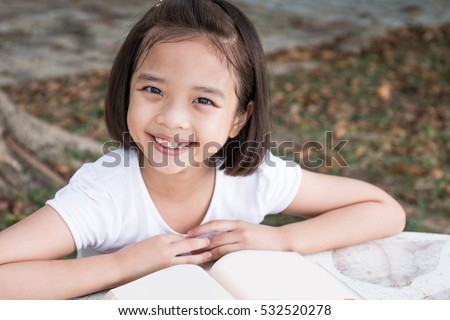 Happy Little Asian child reading a book outdoor