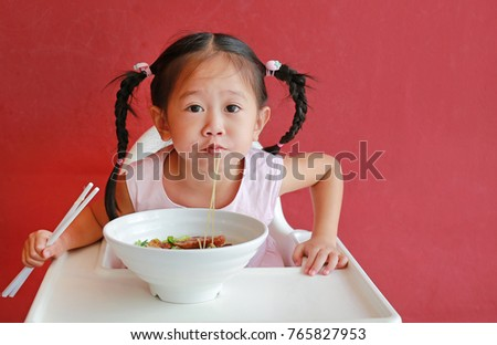 Happy little asian girl eating Egg noodle on high chair against red wall background.