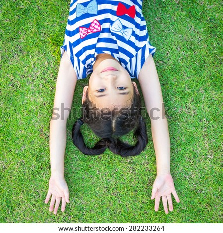 Happy little Asian girl having fun lying on grass floor opening arms up side down : Kid with heart-shaped hair loves beautiful green environment playing outdoor in the park    - stock photo