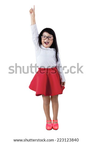 Happy little asian girl raises hand, isolated over white background - stock photo