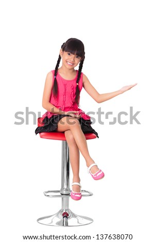 Happy little asian girl sitting on high chair, Isolated over white with clipping path - stock photo