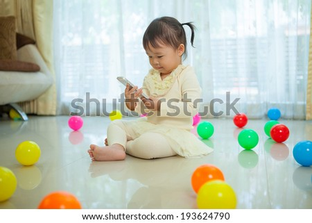 Happy little asian girl using mobile phone in the home - stock photo