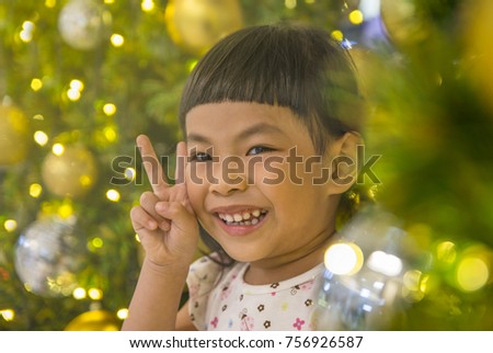 Happy little Asian girl with christmas tree. Golden light ambient.