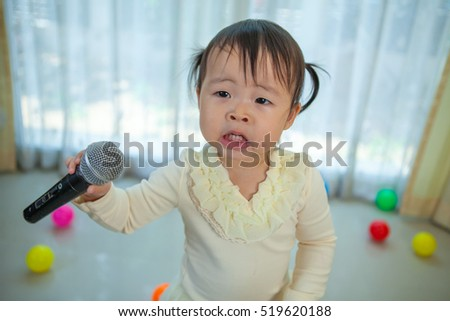 Happy little asian girl with microphone in the home