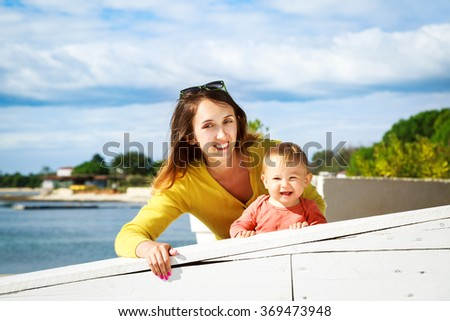 Happy Little Baby and Smiling Mother by the Sea - stock photo