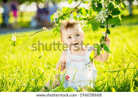 happy little baby boy sitting on a green meadow on the nature in the park - stock photo