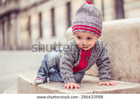 happy little baby boy wearing hat in the city - stock photo