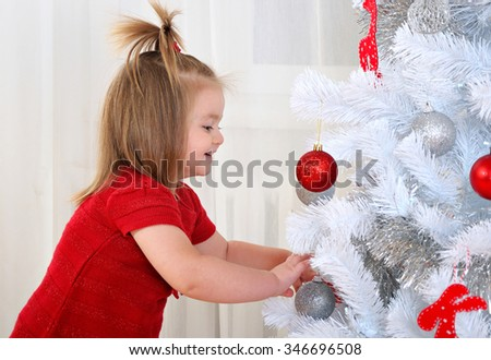 happy little baby girl decorating christmas tree with toys on holidays - stock photo